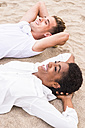 Happy young couple lying side by side on the beach with hands behind head - SIPF01244