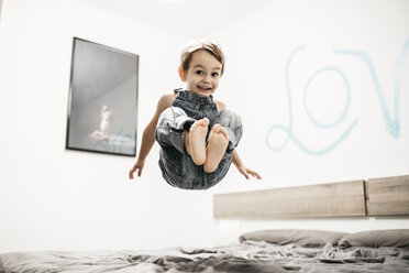 Happy little boy jumping on the bed - JRFF01133