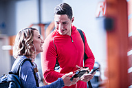 Young man and woman with cell phones and earbuds in gym - ZEF12250