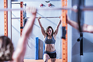 Young woman lifting barbell in gym - ZEF12265