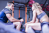 Young man and woman having a refreshment break in gym - ZEF12271