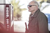 Elderly man holding petrol pump at fuel station - ZEF12301