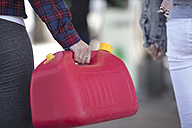 Woman holding canister at fuel station - ZEF12313