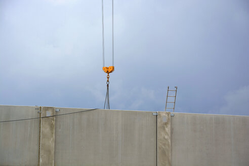 Crane and ladder behind a concrete wall - AXF00785