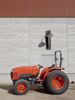 Red tractor parking in front of concrete facade - JMF00391