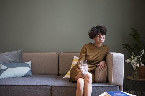 Portrait of smiling young woman with glass of water sitting on couch at home - RBF05444