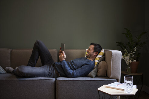 Laughing man using tablet on couch at home - RBF05447