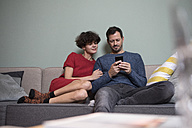 Couple sitting together on the couch looking at cell phone - RBF05450