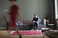 Man sitting on the couch in the living room while his girlfriend passing in the foreground - RBF05453