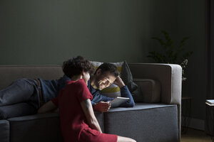 Couple relaxing together in the living room looking at tablet - RBF05459