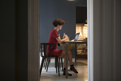 Young woman sitting in the kitchen using laptop - RBF05465