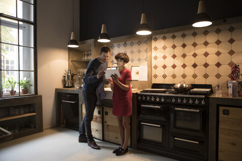 Couple in the kitchen looking at tablet - RBF05471