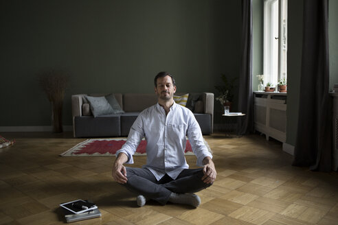 Man meditating on the floor at home - RBF05486