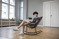 Portrait of smiling young woman sitting on rocking chair at home - RBF05501