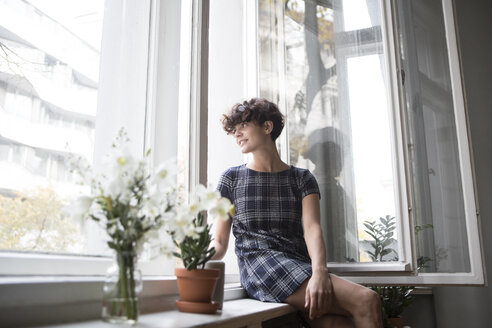 Young woman sitting on window sill  at home - RBF05507