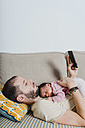 Father lying on the couch with newborn baby girl using smartphone - GEMF01351