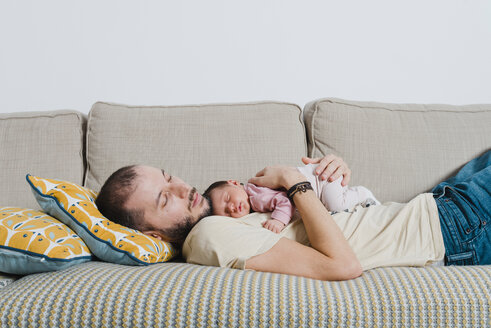 Father and his newborn daughter sleeping on the couch - GEMF01354
