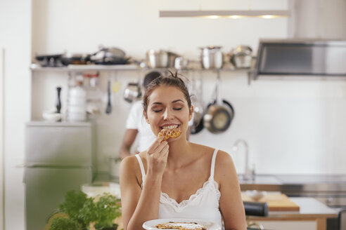 Portrait of young woman eating waffles in the kitchen - FMKF03402