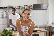 Portrait of laughing young woman with coffee mug in kitchen - FMKF03405