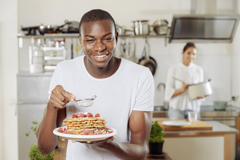 Portrait of young man sprinkling icing sugar on waffles in the kitchen - FMKF03417