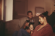 Happy young woman toasting with red wine in the living room - FMKF03420
