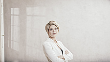 Portrait of blond businesswoman with arms crossed - FMKF03441