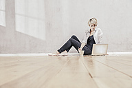 Woman sitting on the floor with coffee cup using laptop - FMKF03444