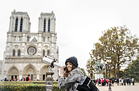 France, Paris, tourist using telescope in front of Notre Dame - MGOF02727