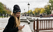 France, Paris, smiling young woman looking at cell phone - MGOF02730