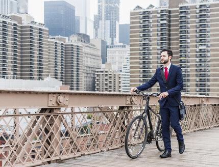 USA, New York City, businessman with bicycle on Brooklyn Bridge - UUF09633