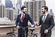 USA, New York City, two businessmen with bicycle on Brooklyn Bridge - UUF09636