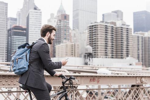 USA, New York City, businessman on bicycle on Brooklyn Bridge using cell phone - UUF09642