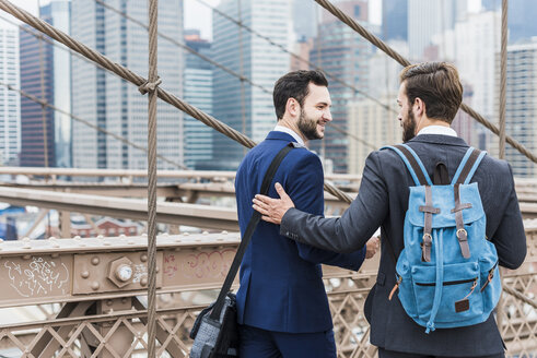 USA, New York City, two businessmen on Brooklyn Bridge - UUF09645