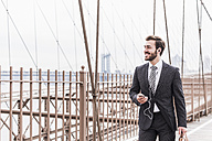 USA, New York City, smiling businessman with cell phone and earbuds on Brooklyn Bridge - UUF09654