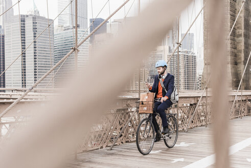 USA, New York City, man on bicycle on Brooklyn Bridge using cell phone - UUF09666