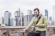 USA, New York City, man on bicycle on Brooklyn Bridge using cell phone - UUF09672