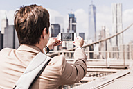 USA, New York City, woman on Brooklyn Bridge taking cell phone picture - UUF09678