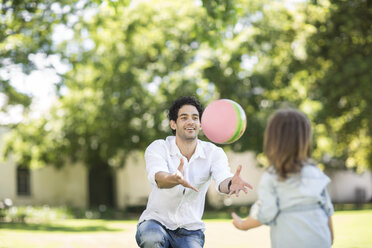 Father playing ball in garden with daughter - ZEF12338