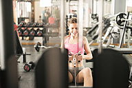 Woman training in gym with rowing machine - JASF01424