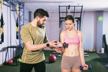 Man training woman lifting weights in gym - JASF01430