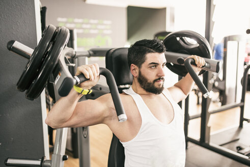 Man exercising with shoulder machine in gym - JASF01433