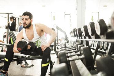 Man training biceps muscle in gym - JASF01436