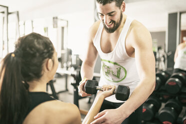 Man training woman lifting weights in gym - JASF01439