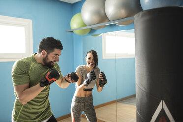 Coach exercising with woman at punching bag - JASF01448