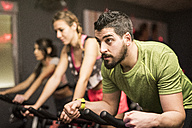 Young people exercising on spinning bikes in gym - JASF01454