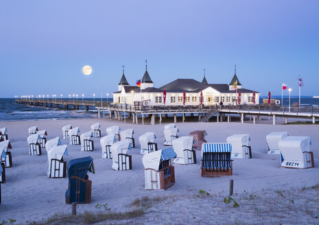 Germany, Usedom, Ahlbeck, view to  sea bridge with hooded beach chairs in the foreground at dusk - SIEF07237