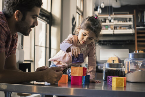 Father and daughter playing with building bricks - WESTF22429