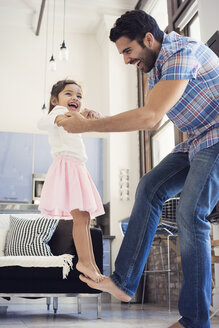 Father balancing his daughter on his foot - WESTF22432