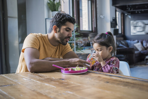Father feeding daughter in kitchen - WESTF22447