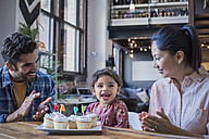 Mother and father eating birthday cup cakes with their little daughter - WESTF22450